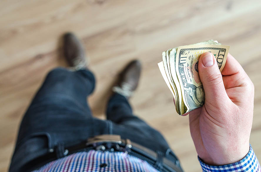 Mann mit Geldbündel in der Hand