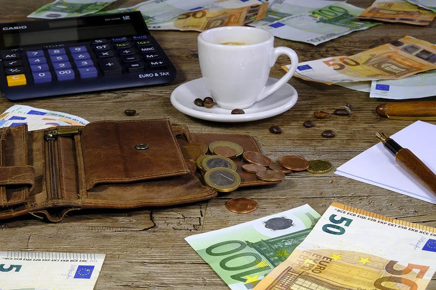 Tisch auf dem Geldscheine und Münzen liegen
