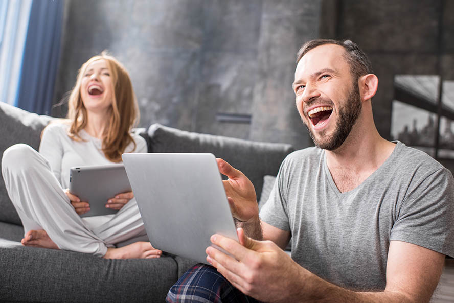 Young couple using digital devices and laughing