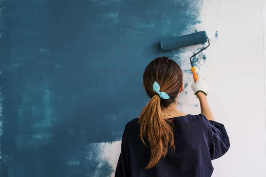 Frau streicht eine Wand neu